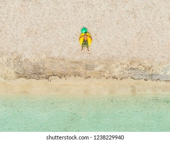 Aerial  view of one man lying on big inflatable pineapple mattress on beach.