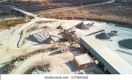 Aerial view of opencast mining quarry with of machinery at work, white quarry stones scattering on the working area in the forest. mine environment, industry background, antropogenic landscape, Russia