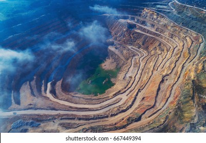 Aerial view of opencast mining quarry with lots of machinery at work - view from above.
