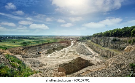 Aerial view of opencast mining quarry with lots of machinery at work - view from above. quarry stones, for construction with blue sky.  mine environment, industry background. rural landscape,
