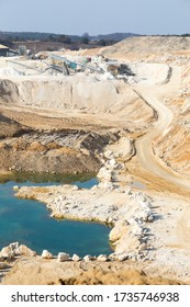 Aerial view of an opencast sand, gravel mine with pond full of green polluted water