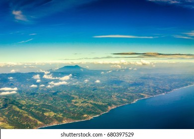 An aerial view out of an airplane window of the pacific coast of El Salvador, Central America