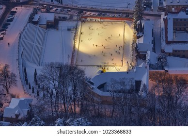 Aerial view of outdoor crowded skating rink, illuminated at twilight, in the historic center of Brasov, at the base of Tampa mountain, Romania.