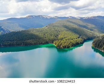 Aerial view over beautiful turquoise mountain lake and green forest. Spring in the mountains. Green forest, mountain lake. Green pine and fir trees forest and a lake. Beautiful spring landscape.