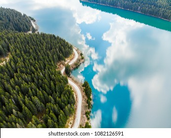 Aerial view over beautiful turquoise mountain lake and green forest. Spring in the mountains. Green forest, mountain lake. Green pine and fir trees forest and a lake. Beautiful mountain road.