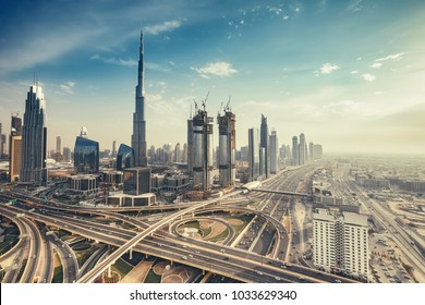 Aerial view over big highway interchange and skyscrapers in Dubai, UAE, at daytime. Scenic cityscape. Toned travel and architectural background.