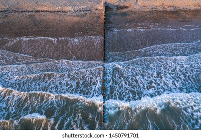 Aerial view over breaking waves on stony shore with wooden breakwater in Barmouth, North Wales, UK