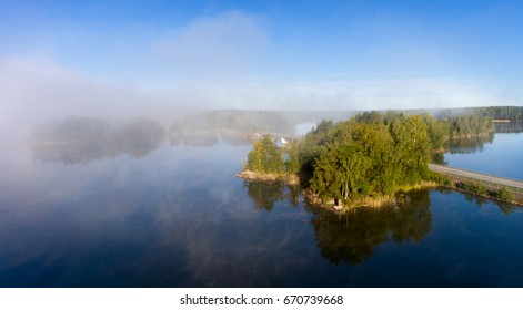 Aerial view over calm lake and bridge in morning mist