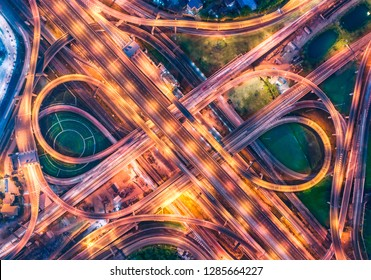 Aerial view over complicate intersection road and express way in Bangkok Thailand at night with long exposure vehicle light trail. Shot by drone.