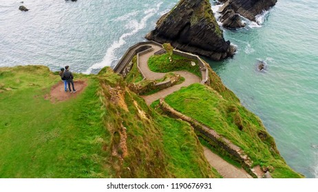 Aerial view over a couple looking over Dunquin pier