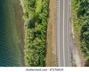 Aerial view over a desolate stretch of highway road alongside a line of trees and the edge of a lake.