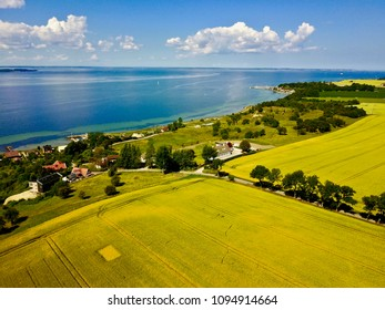 Aerial view over farming field in Sweden with sea in the background