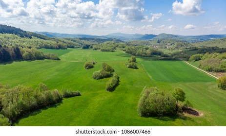 aerial view over the green countryside with tree groves