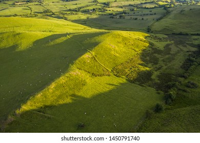 Aerial view over green hills of countryside fields in soft warm sunset light. Shropshire in United Kingdom