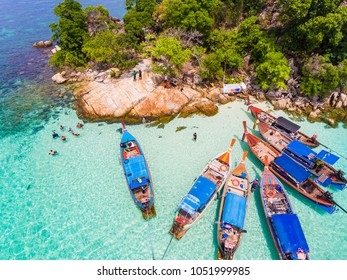 Aerial view over group of long tail boats with beautiful sea island and beach,Top view from drone, Koh Lipe island, Satun,Thailand.