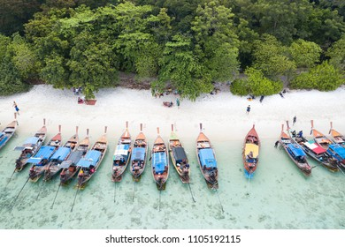Aerial view over group of long tail boats with beautiful sea and beachTop view from drone Koh Lipe island, Satun Province, Thailand.