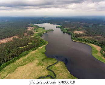 Aerial view over Latazeris lake with a curvy river stream from the forest near the border, Lithuania. During cloudy summer day.