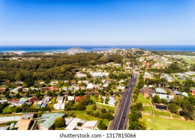 Aerial view over local regional town Coffs Harbour on Australian Middle North Coast of NSW towards Pacific ocean waterfront over local suburbs, streets, houses and parks.