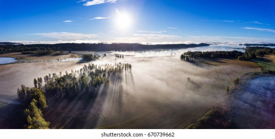 Aerial view over misty fields and lake in morning in Finland
