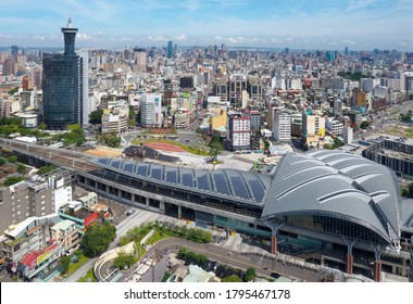 Aerial view over the modern & futuristic architecture of Taichung Train Station in downtown, with high rise towers standing among crowded buildings under blue sunny sky, in Taichung, Taiwan, Asia