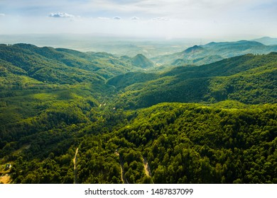 Aerial view over mountains, golden, green mountains and misty clouds in Europe