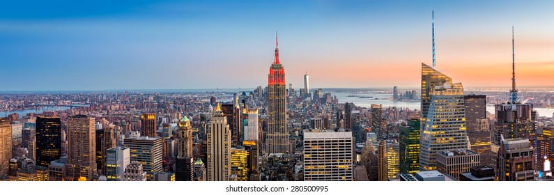 Aerial view over New York City at sunset. The Empire State Building is colored in red to honor the New York City Fire Department (FDNY)