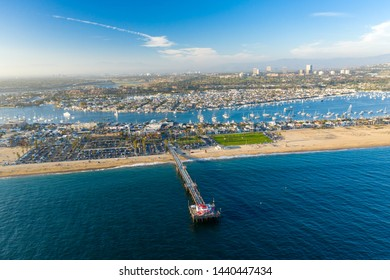 Aerial view over Newport Beach in coastal Orange County, California on a sunny day from above with the ocean, pier and harbor in view.