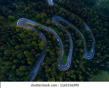 Aerial view over old patched two lane forest with the cars. Cars driving along the forest. Winding road in the mountain forest. Great road trip in the dense woods. Serpentine road with trafic.