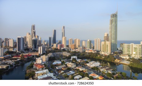 Aerial view over Paradise Island towards Surfers Paradise cityscape with sunset light hitting the skyline.