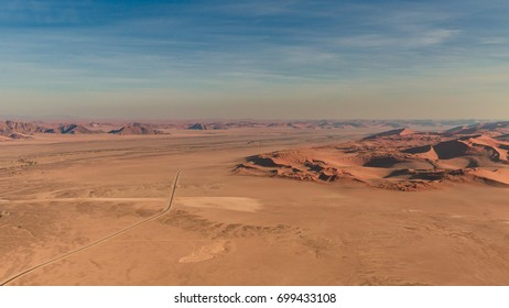 aerial view over the road withing the dunes of the Namib desert at Sosusvlei.  Annual growth of the area of sand. Global warming on the planet. Climatic changes on Earth.