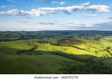 Aerial view over rolling hills of countryside fields in soft warm light. Shropshire in United Kingdom