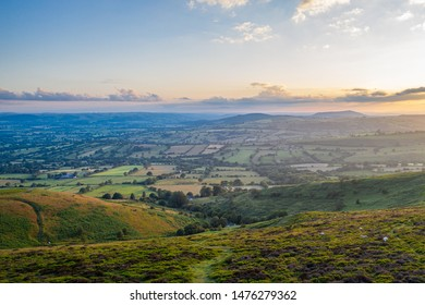 Aerial view over scenic farming hills in subtle sunset light. Shropshire in United Kingdom