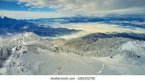 Aerial view over the spectacular ski slopes in the Carpathians mountains, Panoramic view over the ski slope Poiana Brasov ski resort in Transylvania,Romania,Europe,Pine forest covered in snow