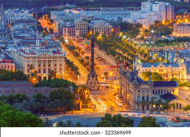 Aerial view over square Portal de la pau, and Port Vell marina and Columbus Monument at night in Barcelona, Catalonia, Spain.