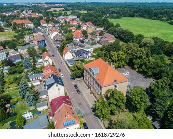 Aerial view over the village of Knautkleeberg close by the city of Leipzig, Germany. Drone shot over the suburbs of Leipzig. In the background the skyline of Leipzig is seen. The green belt of Leipzig