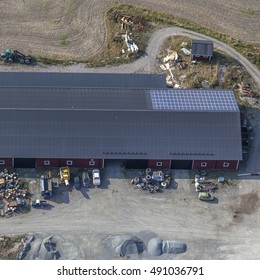 Aerial view over a workshop, factory, recycling facility, warehouse, Outside the building a tractor is harvesting the field. Solar panels on the roof. Old tiers outside the warehouse.