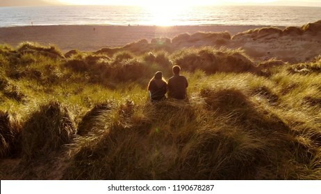 Aerial view over a young couple sitting on the beach at sunset