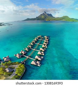 Aerial view of overwater bungalow villas with thatched roofs in the Bora Bora lagoon in French Polynesia