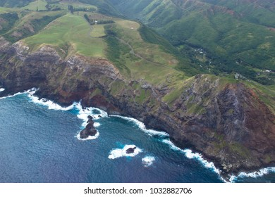 Aerial view of Pacific surf, rocky cliffs, and green meadows on the coast of the island of Maui in Hawaii
