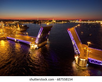 Aerial view of Palace drawbridge is drawn before water transport navigation in St. Petersburg, Russia, Hermitage museum on background, the white nights, a lot of ships, square, night illumination