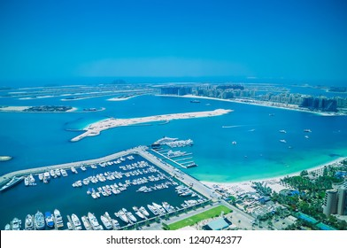 Aerial view of Palm Jumeirah Island with luxury yachts in the front. Development of Dubai.