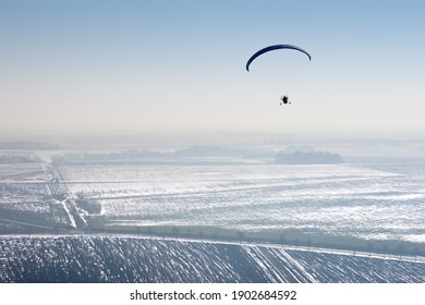 Vue aérienne d'un paramoteur volant au-dessus de l'immensité des champs de neige hivernaux français avec horizon et ciel bleu