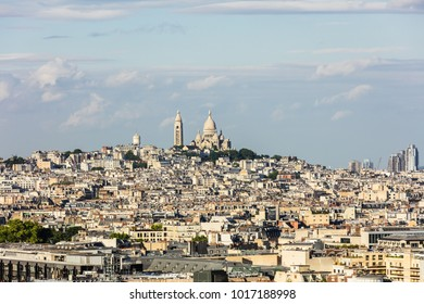 Aerial view of Paris cityscape with Basilica of the Sacred Heart of Paris (Basilique du Sacre Coeur) on Montmartre hill from the top of Triumphal Arch of the Star at the summer sunset. Paris, France