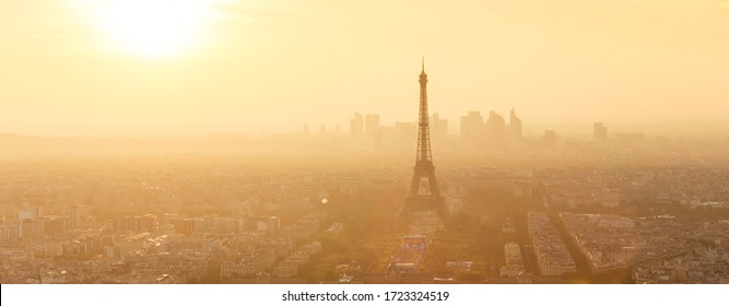 Aerial view of Paris with Eiffel tower and major business district of La Defence in background at sunset.