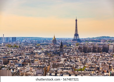 Aerial view of Paris with Eiffel Tower on background. Grey rooftops in Paris, with the golden dome of Les Invalides and the famous tower. Travel and architecture concepts