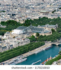 Aerial view of Paris; the Grand Palais, Petit Palais and Madelaine church with tourist boats on Seine river