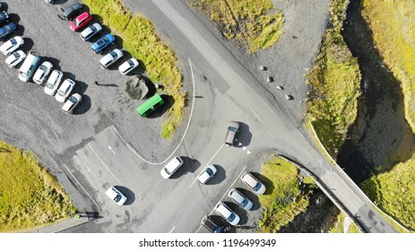 Aerial view of a parking lot amidst lush green fields in Iceland