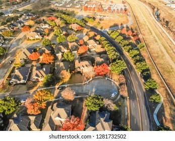 Aerial view parkside neighborhood with cul-de-sac (dead-end) street near Dallas, Texas. Flyover urban sprawl in autumn morning with colorful fall foliage leaves