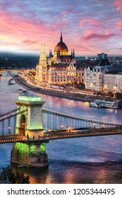 Aerial view of the Parliament building at sunset in Budapest, Hungary. Green light on the Chain Bridge pillar.