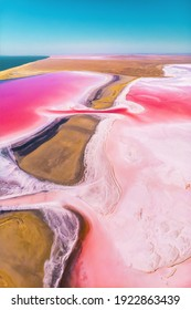 Aerial view of a partially dried up salt lake divided by an oblique sunny day. Natural extraction of pink salt